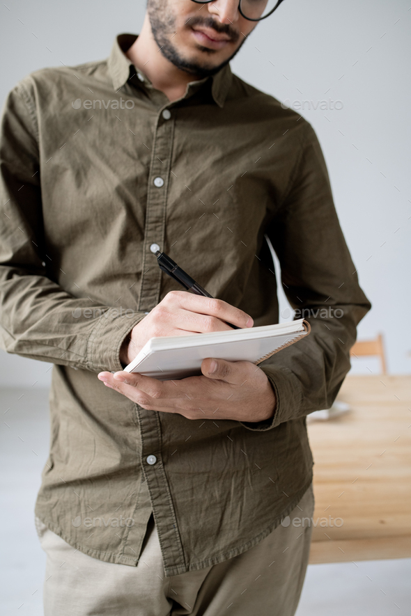Young serious male employee making notes in notebook while organizing work - Stock Photo - Images
