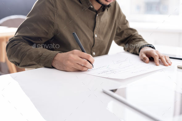Young busy economist drawing flow chart on paper while preparing report - Stock Photo - Images