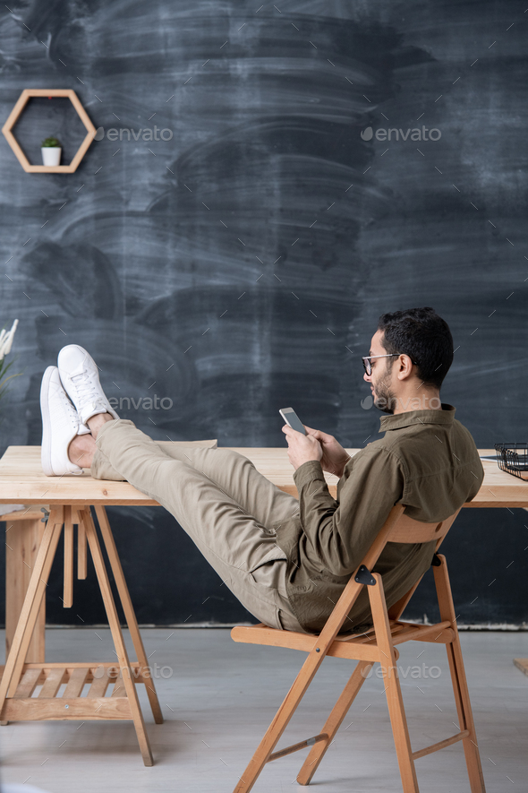 Young casual employee keeping legs on table while scrolling in smartphone - Stock Photo - Images