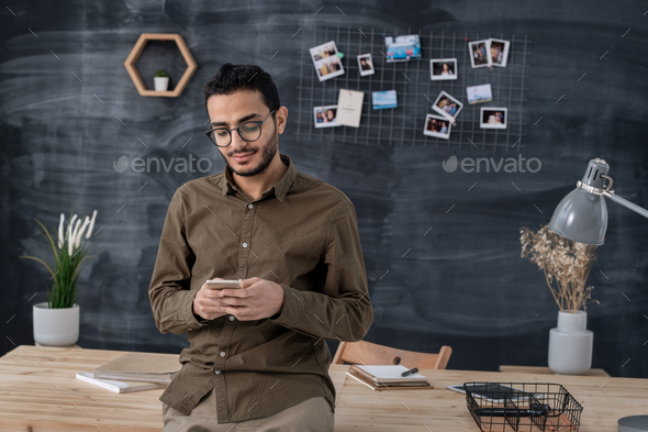 Young confident businessman in casualwear scrolling in smartphone in office - Stock Photo - Images