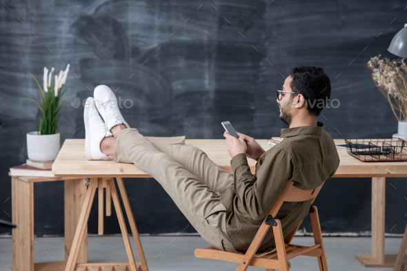 Young employee in casualwear keeping legs on table while scrolling in smartphone - Stock Photo - Images