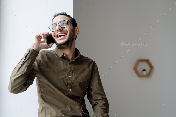 Happy young casual businessman talking on mobile phone by office window - Stock Photo - Images