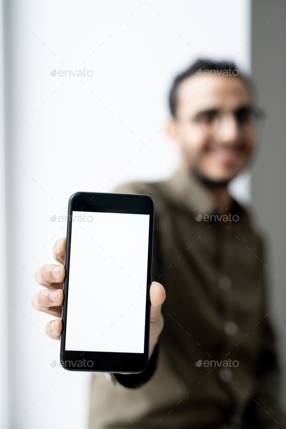 Smartphone with blank touchscreen in hand of young contemporary businessman - Stock Photo - Images