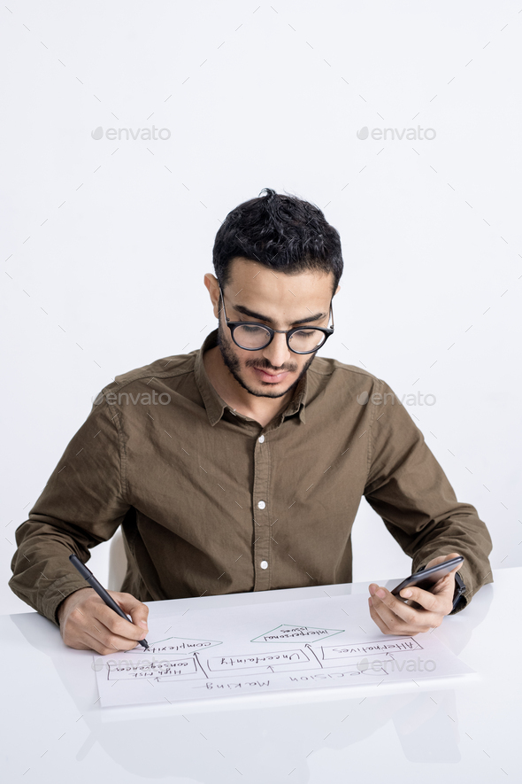 Young confident businessman with smartphone and pen drawing flow chart on paper - Stock Photo - Images