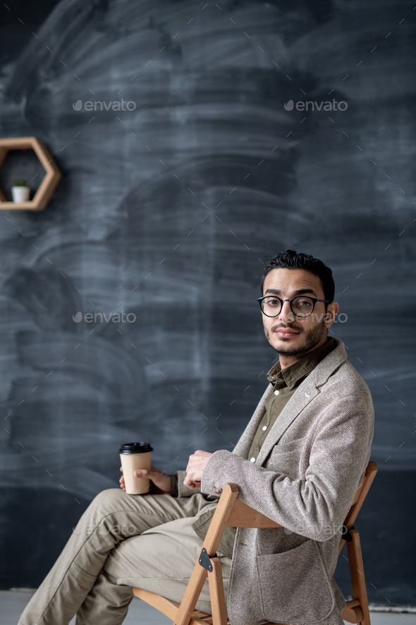 Contemporary businessman with glass of coffee sitting on chair in isolation - Stock Photo - Images