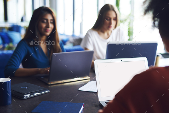 Blurred view of coworkers working at office desk - Stock Photo - Images