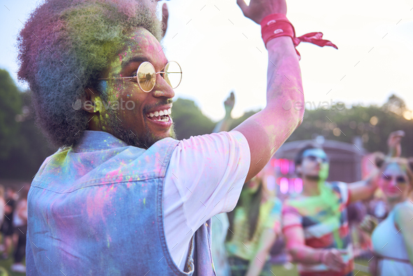 African man in holi colors dancing during music festival - Stock Photo - Images