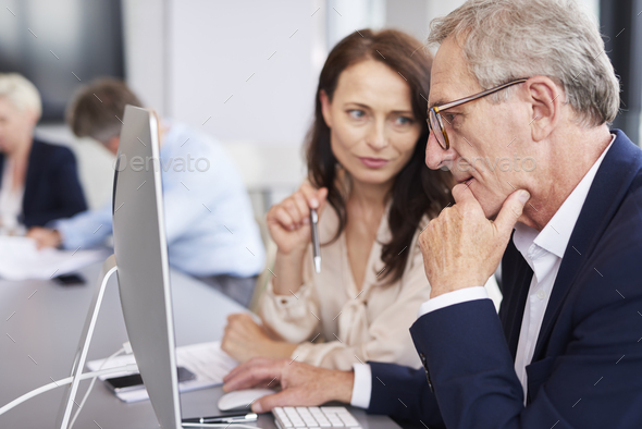 Busy businessman using a computer during business meeting - Stock Photo - Images