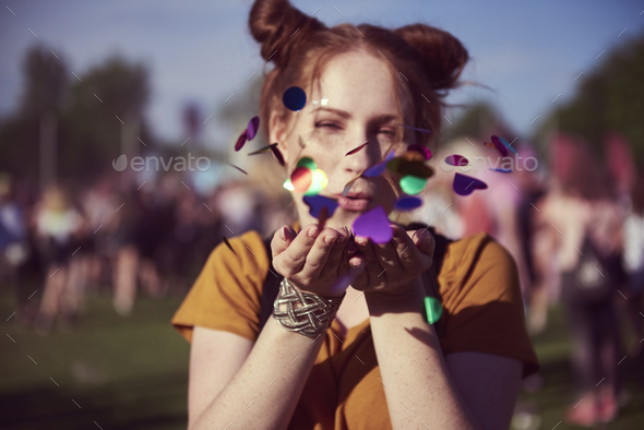 Girl blowing some confetti pieces - Stock Photo - Images