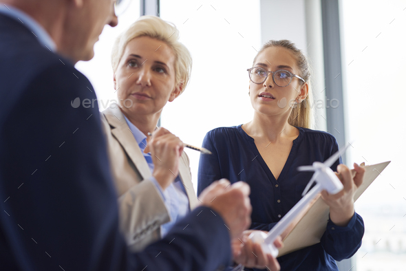 Busy office workers having a conversation in the office - Stock Photo - Images