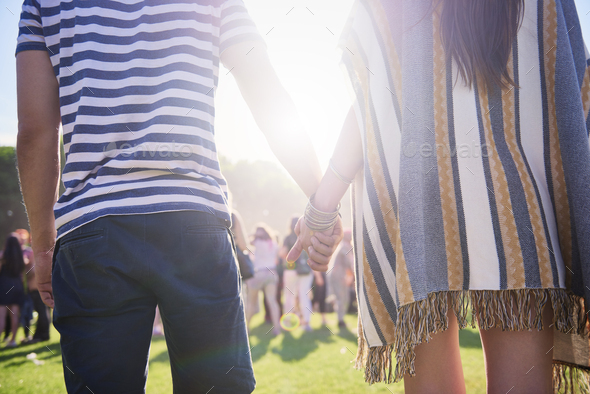 Rear view of couple holding hands in festival - Stock Photo - Images