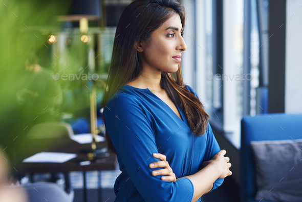 Beautiful Asian woman looking through window in the office - Stock Photo - Images
