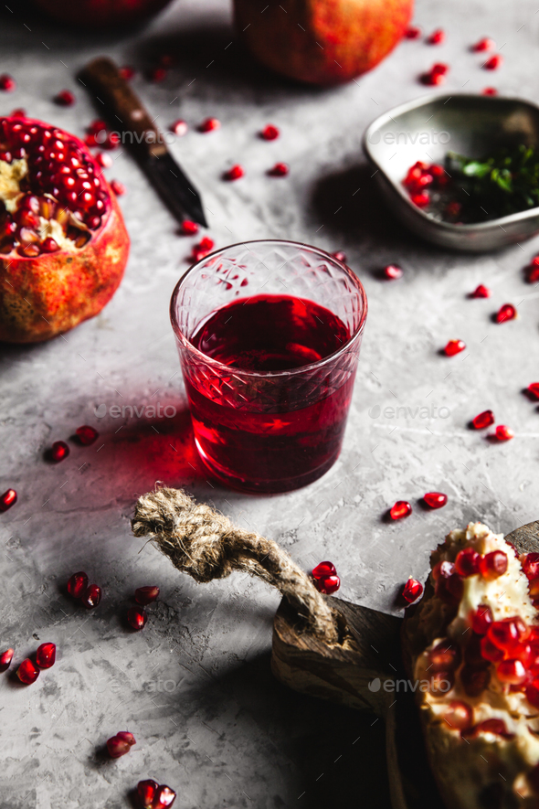 Red pomegranate juice in a glass, ripe and cut pomegranate and a sprig of mint on a gray background - Stock Photo - Images