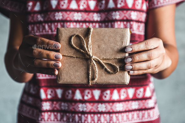 Female wearing a red with red christmas dress has a christmas gift in her hands - Stock Photo - Images