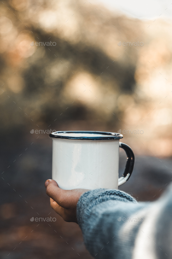 hand holding cup of coffee on natural background - Stock Photo - Images