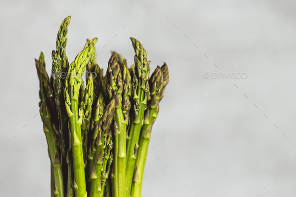 Fresh bunch of asparagus with smooth daylight on grey stone background/top view - Stock Photo - Images