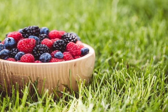 raspberries and blackberries in wood bowl on table, vintage - Stock Photo - Images