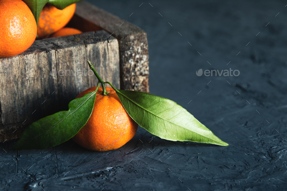 Box with tasty juicy tangerines in wood box on dark background with copy space - Stock Photo - Images