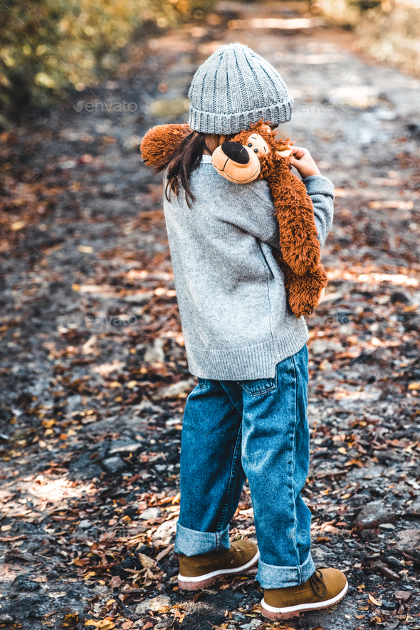 Little girl hugs her bear on a background of nature, autumn, durba - Stock Photo - Images