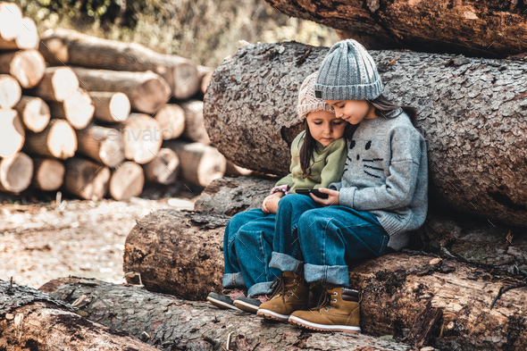 Children in the background of logs play with a smartphone. Watch the video and have fun. Friendship - Stock Photo - Images