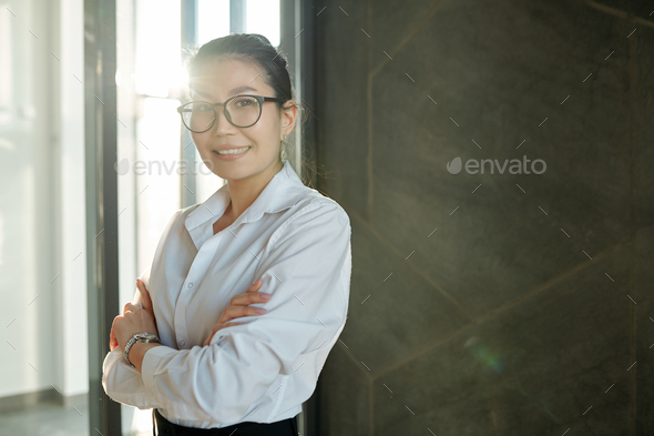 Pretty young smiling businesswoman of Asian ethnicity crossing arms by chest - Stock Photo - Images