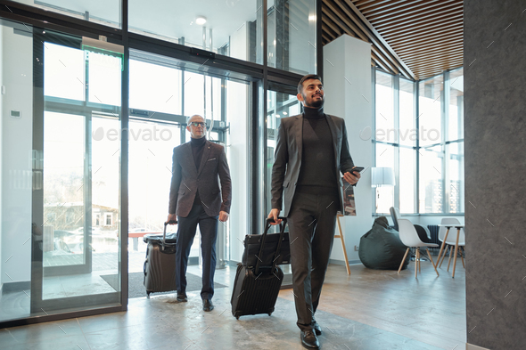 Two elegant business travelers pulling suitcases while entering hotel lounge - Stock Photo - Images