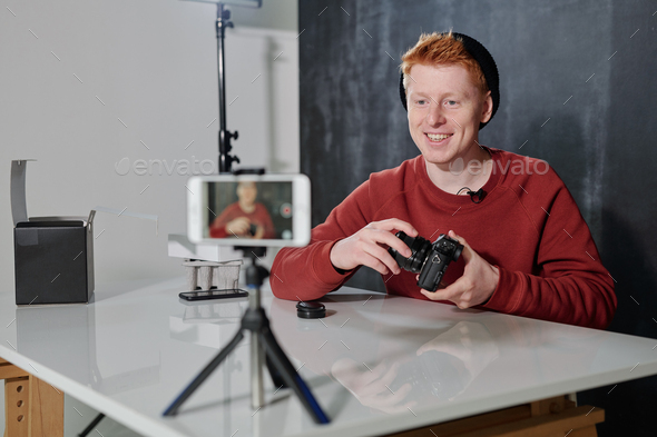 Young cheerful man in casualwear presenting his new photocamera in studio - Stock Photo - Images