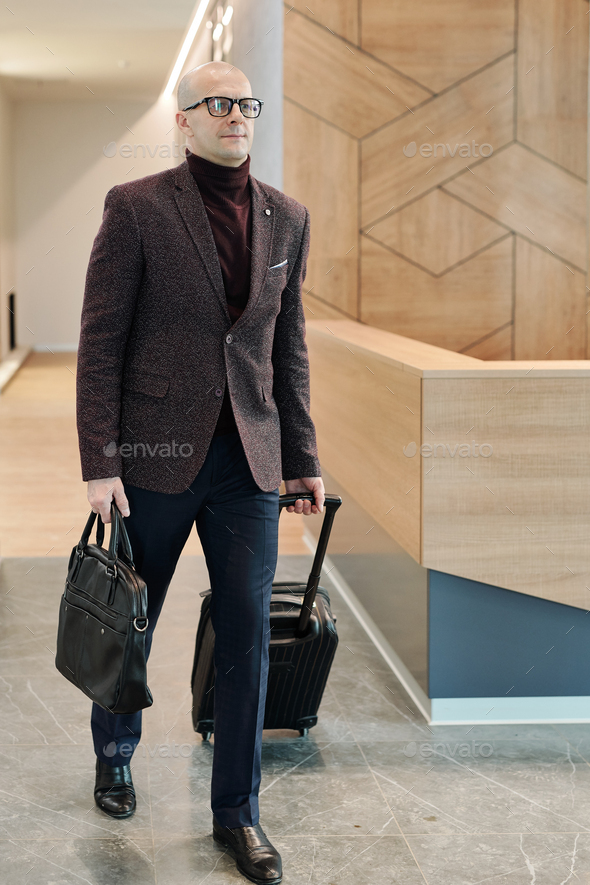 Bald mature businessman pulling suitcase while moving along reception counter - Stock Photo - Images