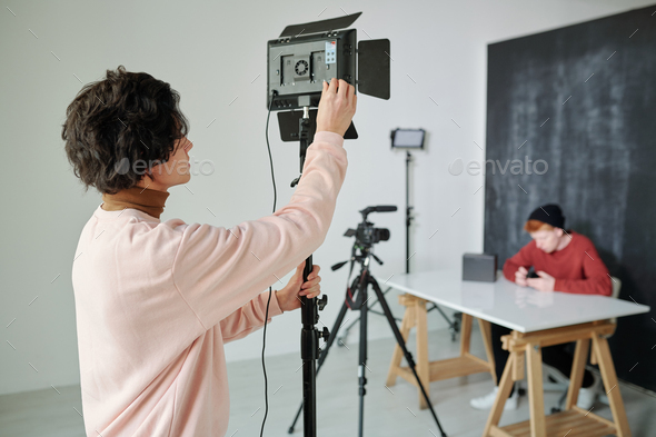Young cameraman in casualwear preparing video shooting equipment - Stock Photo - Images