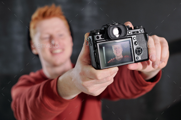 Hands of cheerful young vlogger holding camera in front of himself in studio - Stock Photo - Images