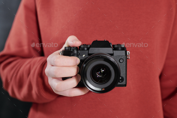 Hands of contemporary male photographer with new photocamera by chest - Stock Photo - Images