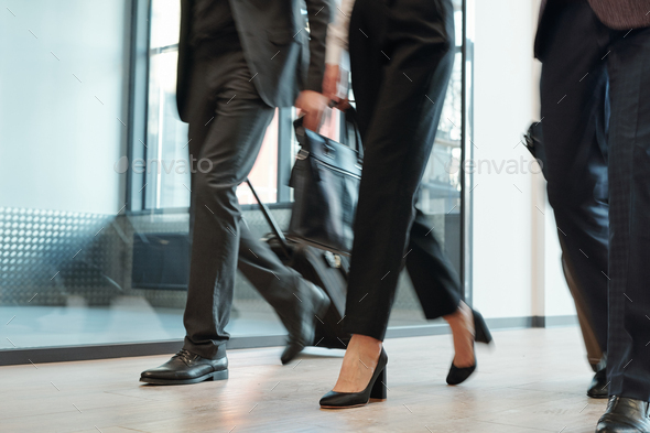 Legs of elegant business travelers in formalwear pulling their baggage - Stock Photo - Images