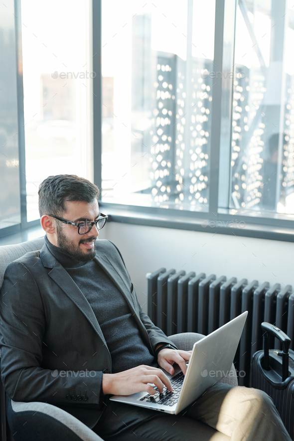 Young successful businessman in suit sitting in armchair in front of laptop - Stock Photo - Images