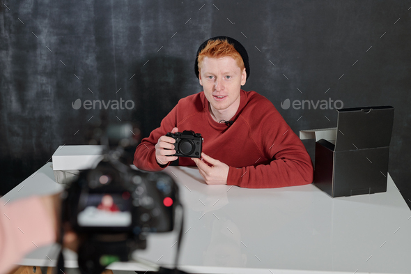 Young man in casualwear sitting by desk and talking about new photocamera - Stock Photo - Images