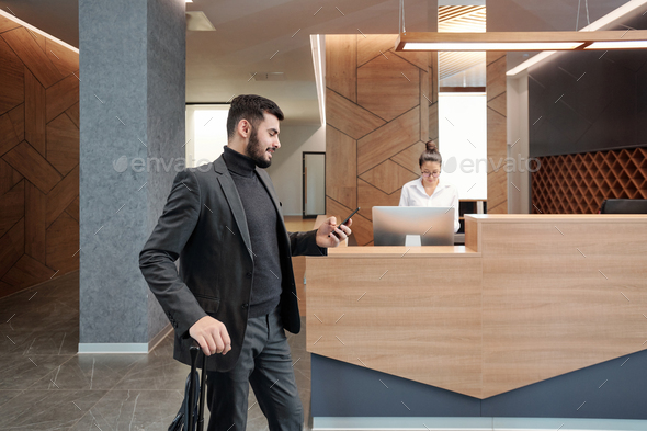 Young business traveler with suitcase scrolling in smartphone in hotel lounge - Stock Photo - Images