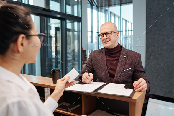 Bald businessman with pen looking at female receptionist while filling in form - Stock Photo - Images