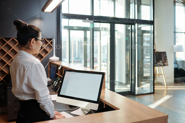 Young female receptionist standing in front of computer screen by counter - Stock Photo - Images