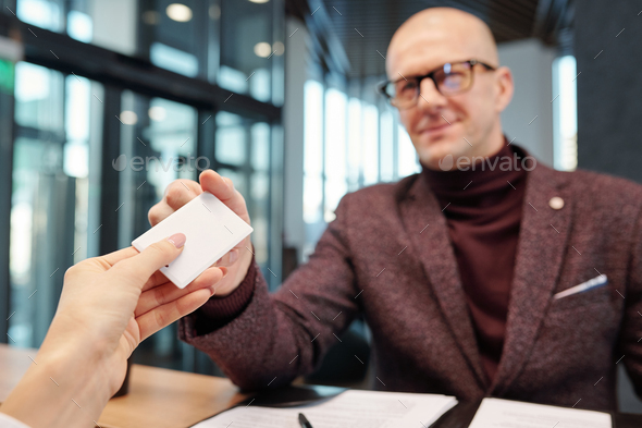 Hand of businessman taking card from empty hotel room at reception counter - Stock Photo - Images