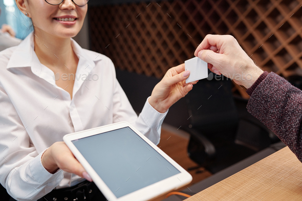 Young receptionist with touchpad passing card from hotel room to businessman - Stock Photo - Images
