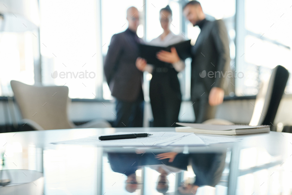 Pen on papers and notebook with business partners having negotiation - Stock Photo - Images