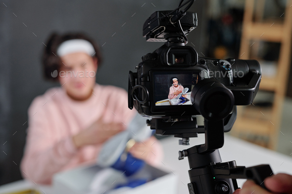 Young vlogger in casualwear showing sneakers on display of digital video camera - Stock Photo - Images