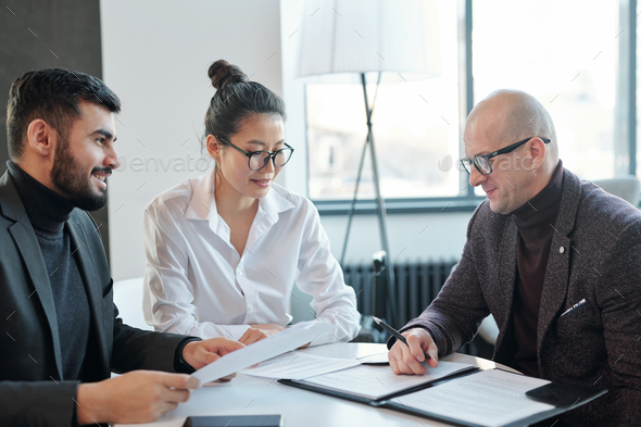 Mature agent consulting his business partners looking through financial contract