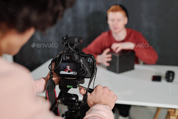 Hands of young operator by camera shooting contemporary male vlogger - Stock Photo - Images