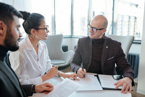 Young Asian female agent looking at business partner going to sign contract - Stock Photo - Images