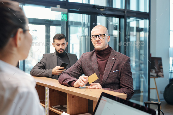 Bald mature business traveler with plastic card ordering room for night in hotel - Stock Photo - Images