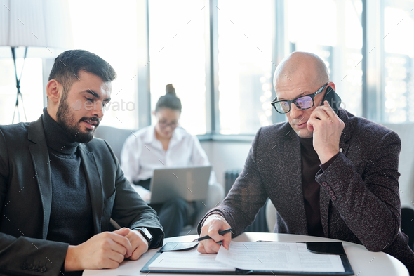 Busy broker in formalwear looking through papers and consulting client by phone - Stock Photo - Images