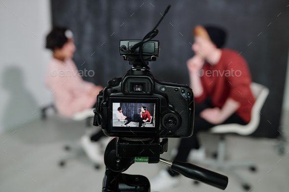 Screen of digital video camera with two vloggers sitting on chairs and talking - Stock Photo - Images