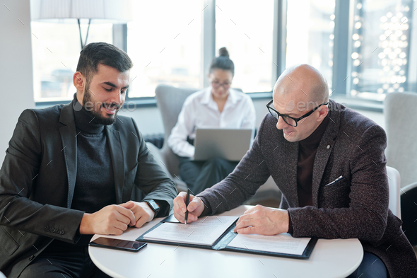Two successful business partners signing financial documents in hotel lounge - Stock Photo - Images