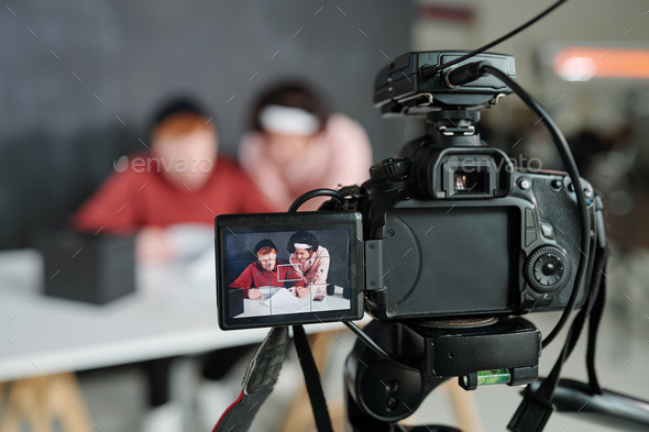 Two young contemporary male vloggers on screen of video camera in studio - Stock Photo - Images