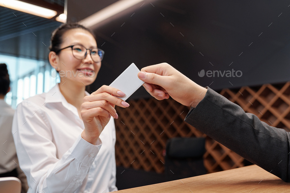 Hand of young receptionist passing card from hotel room to business traveler - Stock Photo - Images